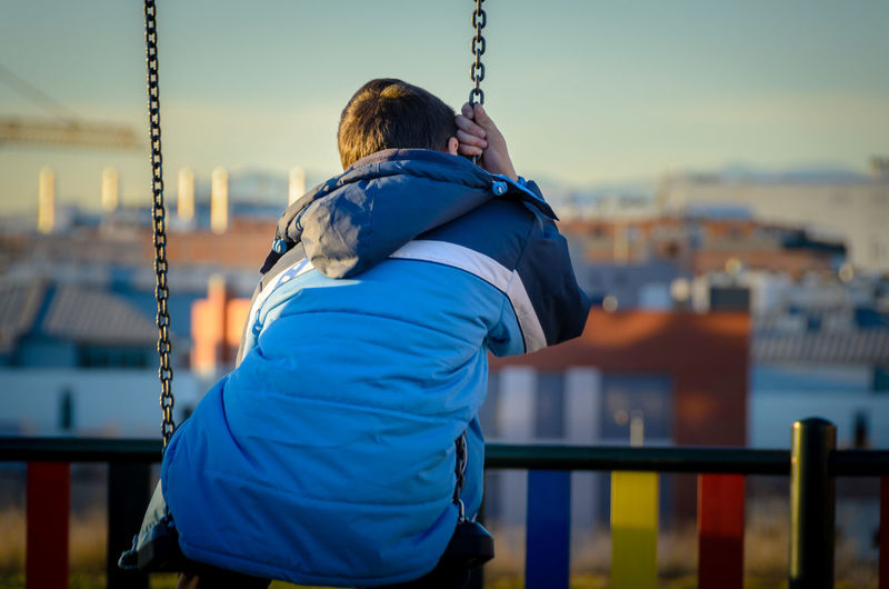 Rear view of boy sitting on swing at park