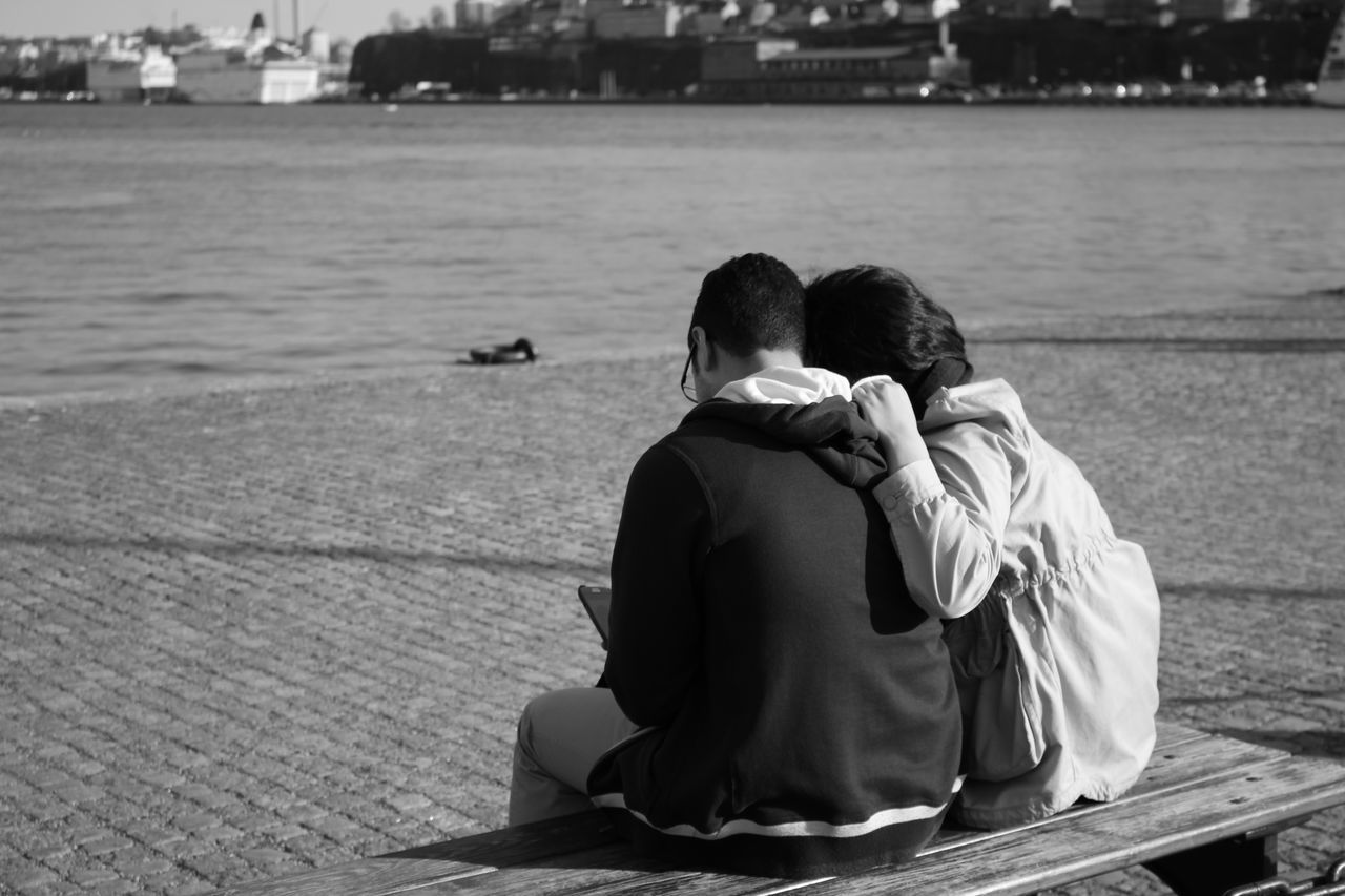 two people, togetherness, love, rear view, real people, sitting, men, water, bonding, sea, day, outdoors, boys, women, couple - relationship, lifestyles, retaining wall, nature, friendship, adult, people