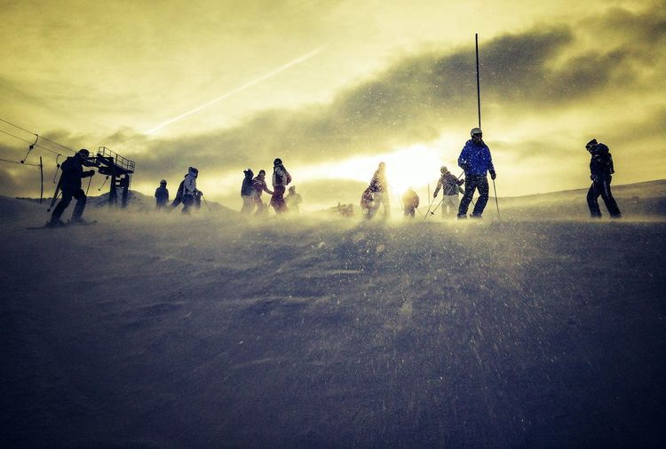 Group of people on snowy field against sky