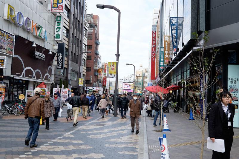 People Walking On Street Amidst Buildings