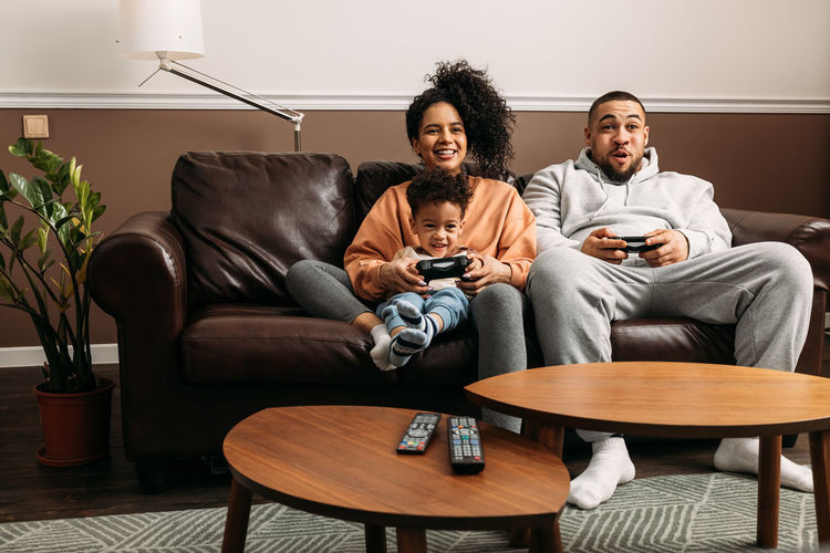 Mother and father with son playing video game while sitting on sofa at table