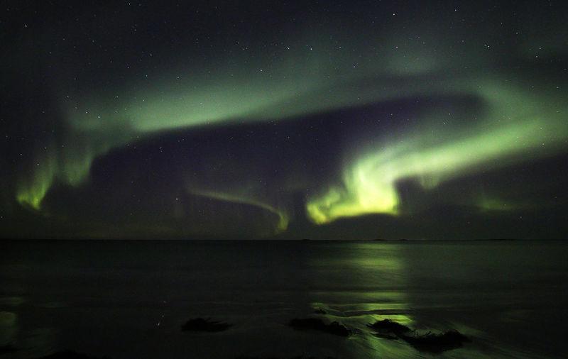 Scenic view of aurora borealis over sea at night