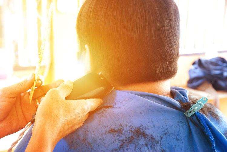Rear view of man getting haircut at barber shop