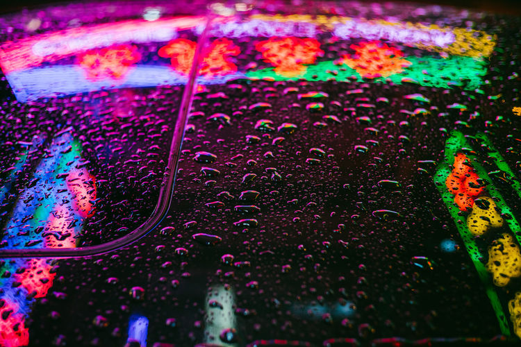 High angle view of water drops on multi colored glass