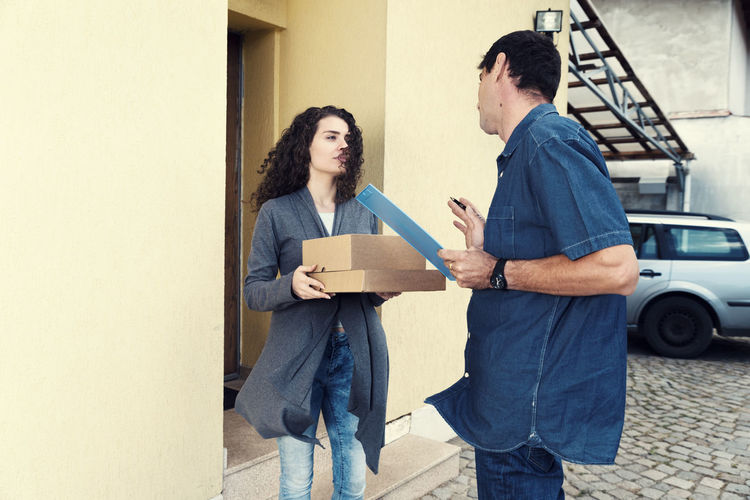 Woman And Delivery Man Talking Against House