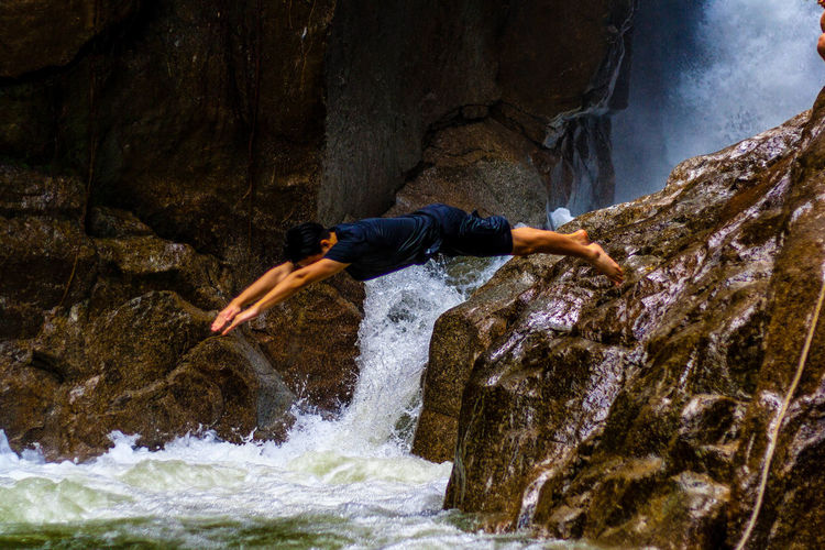Side view of man jumping in river