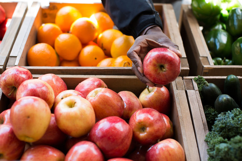 Cropped Image Of Hand Holding Apple At Market Stall