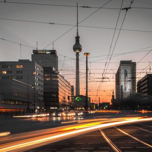 Light trails on city street against sky