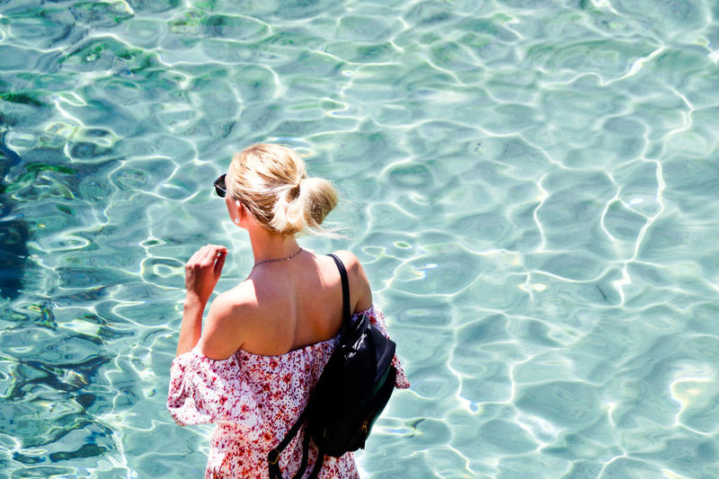 Rear view of woman standing in swimming pool