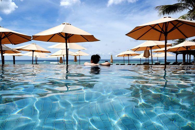 Woman relaxing in infinity pool against sky