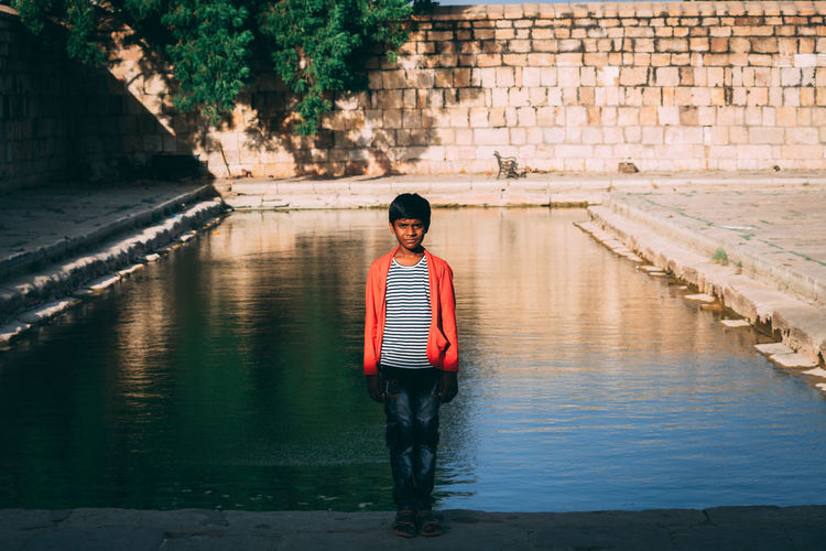 Full length of boy standing on wall by canal