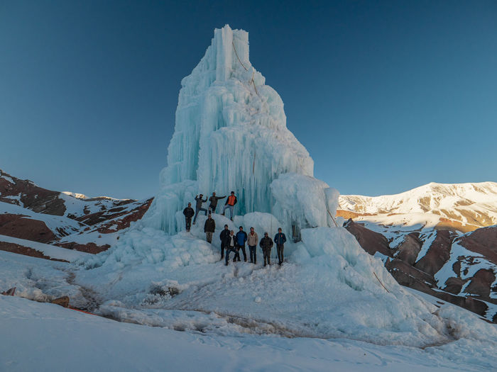 Group of people on snowcapped mountain against sky