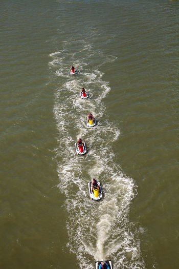 High angle view of people jet boating in sea
