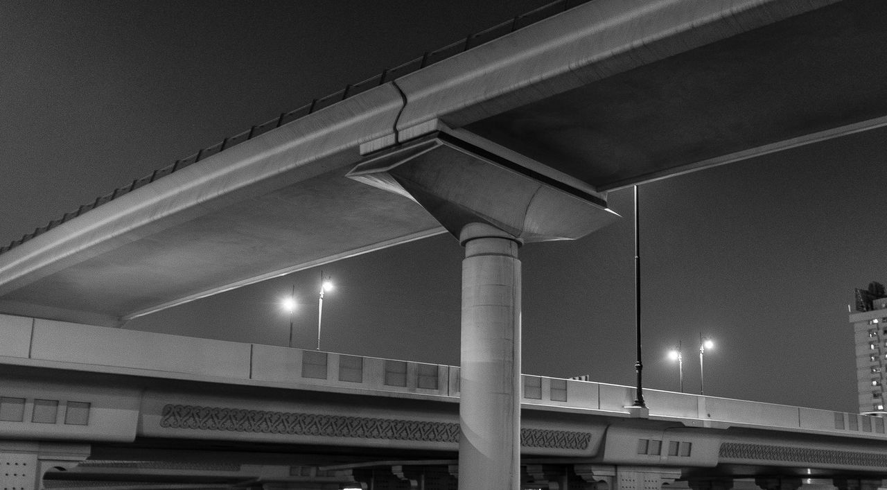 Low Angle View Of Overpass By Illuminated Street Lights Against Clear Sky