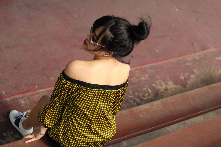 Rear view of woman sitting against wall