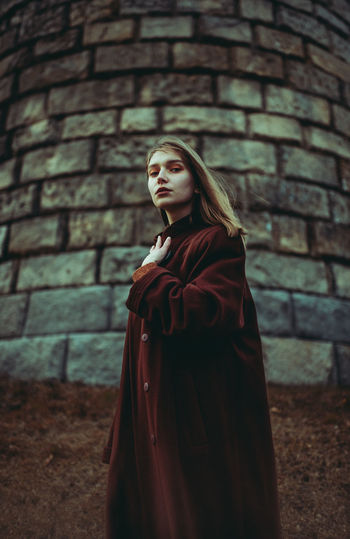 Young woman looking away against brick wall