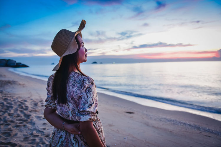 Woman standing at beach against sky during sunset