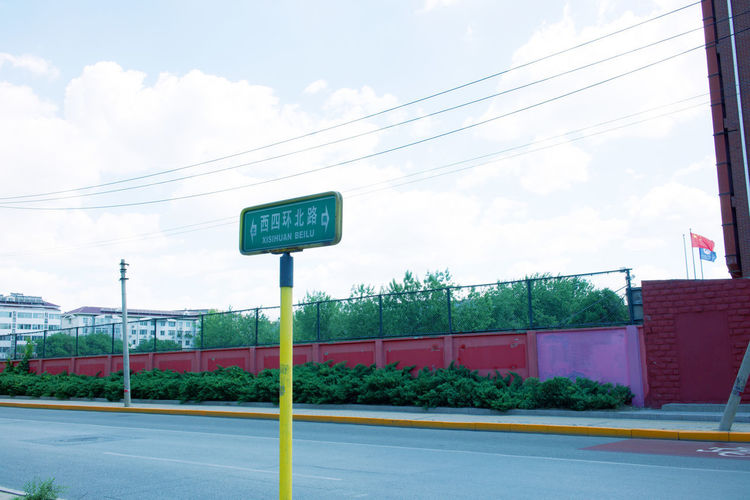 Road sign by street against sky