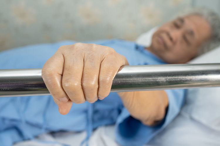 Senior woman lying down on bed while holding railing in hospital