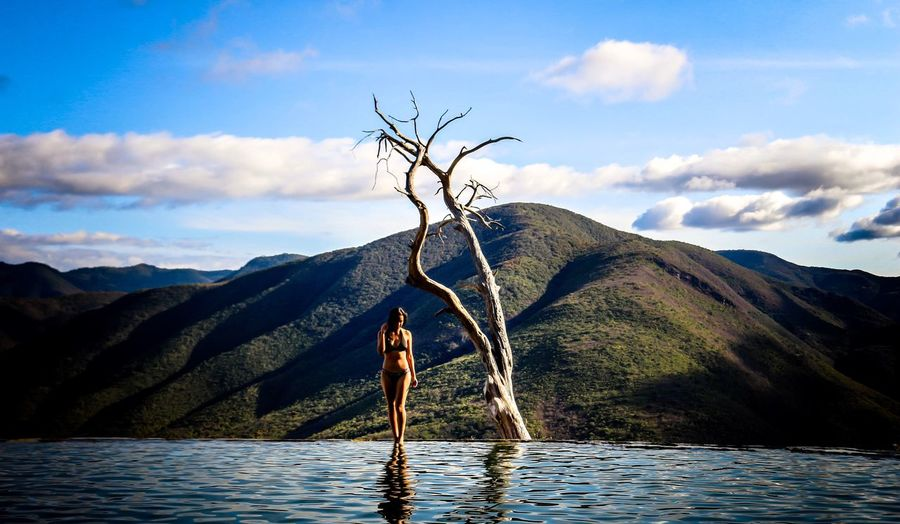 Full length of woman standing by infinity pool against sky