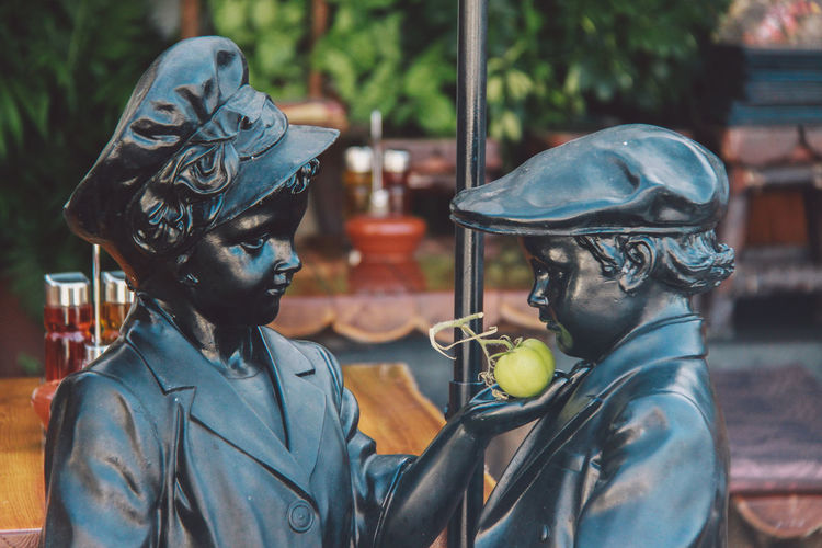 Close-Up Of Statues With Green Tomato