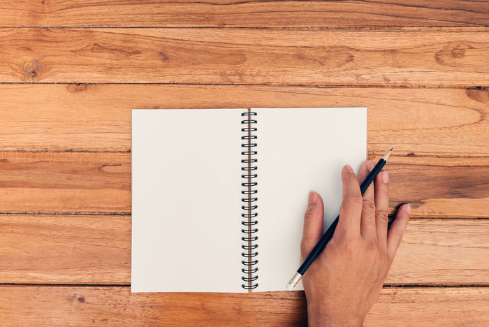 Blank Book Close-up Copy Space Day Desk Diary Directly Above Drawing - Activity Human Body Part Human Hand Indoors  Note Pad One Person Page Paper Pen Pencil Pencil Drawing People Sketch Pad Table Wood - Material Writing