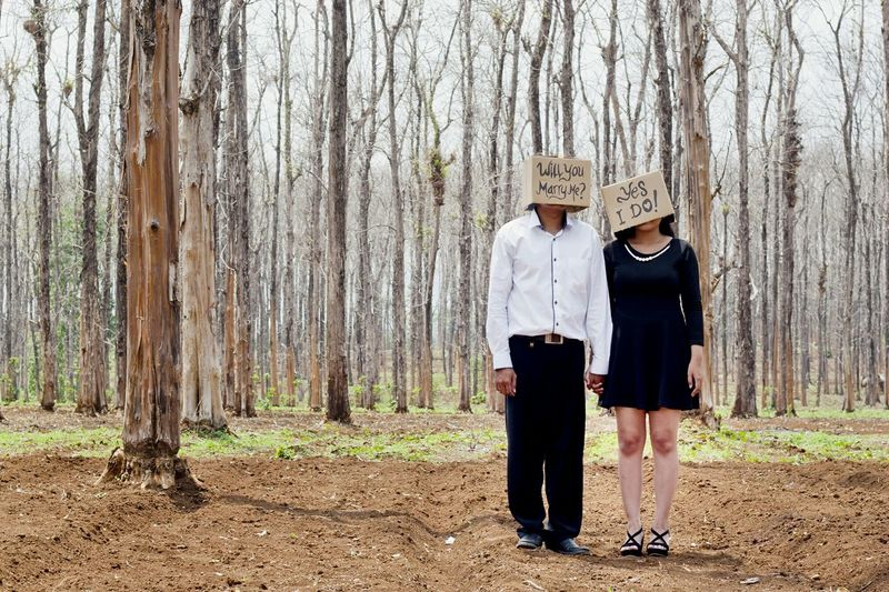 Couple wearing boxes with text while standing in forest