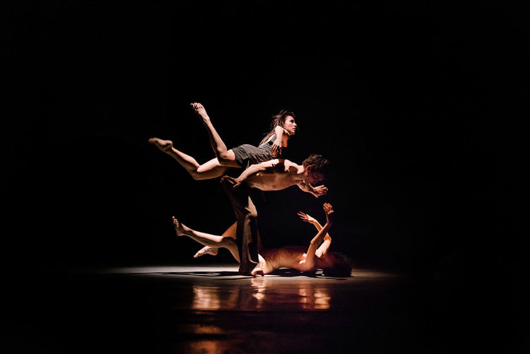 Low angle view of person dancing against black background