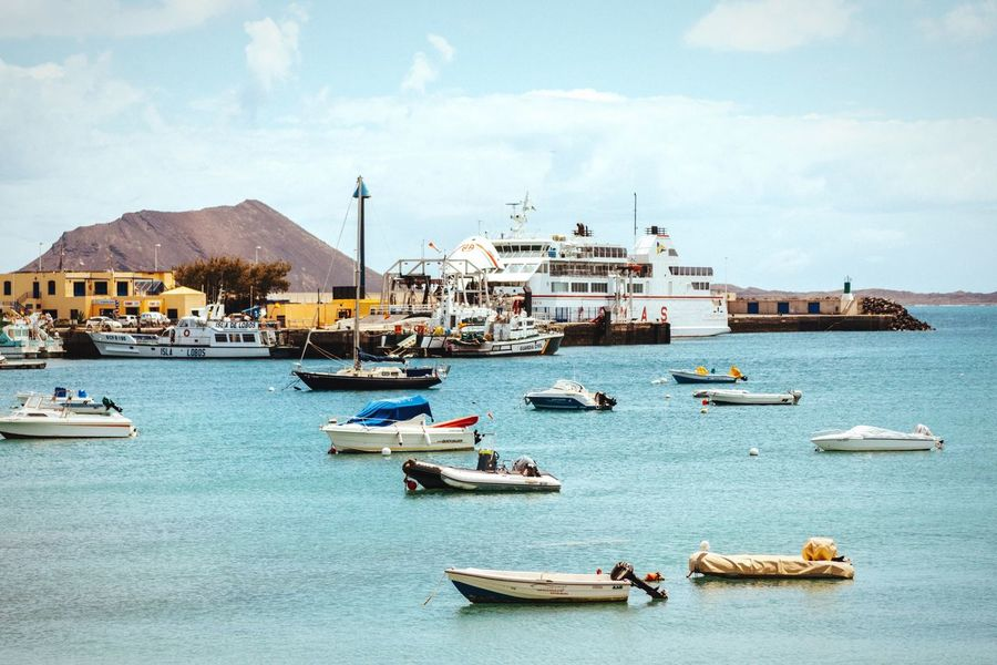 Several boats The Color Of Business Nautical Vessel Transportation Mode Of Transport Boat Waterfront Water Sky Sea Cloud - Sky Outdoors Harbor Sailing Journey Harbour Town Boats Sailboat Sailing Ship Fuerteventura Blue Sky Port Dock Tranquility Canary Islands Corralejo