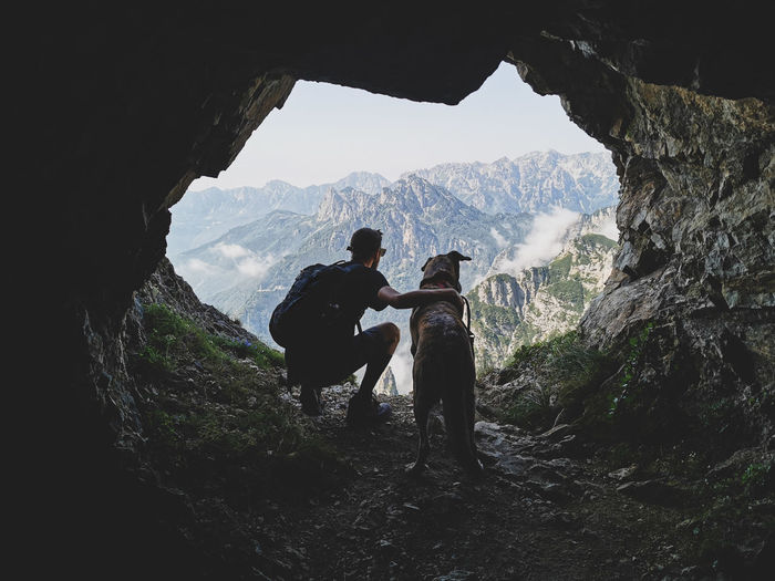 Men with dog against mountains