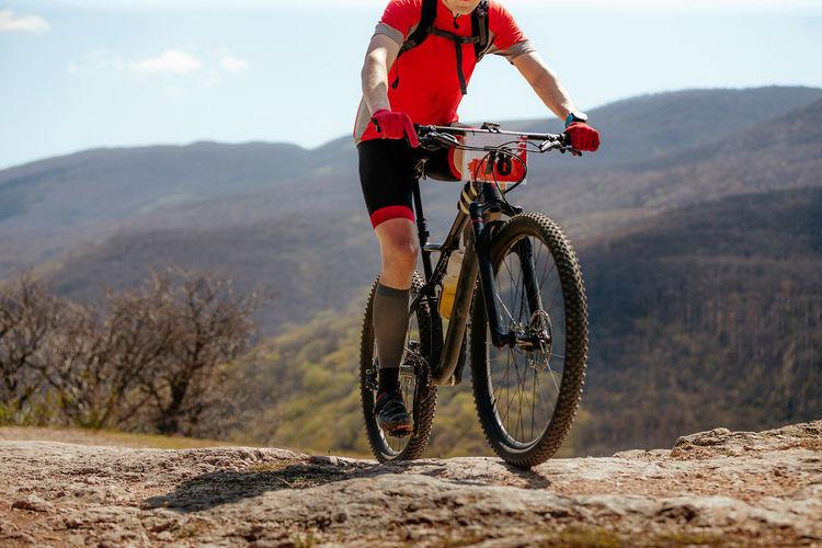 Male athlete on mountain bike biking in background of mountain