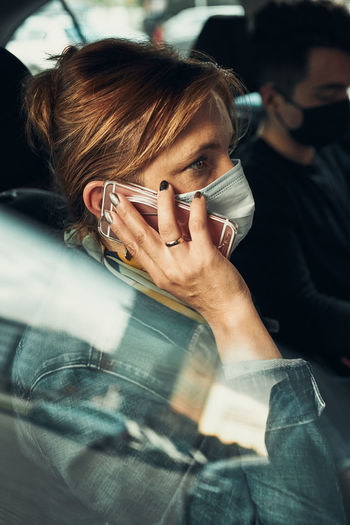 Woman talking on phone using smartphone sitting in a car wearing the face mask to avoid virus