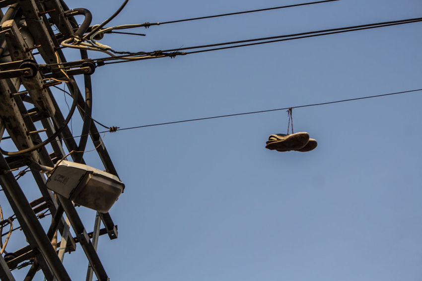 What happened in the neighborhood? Blue Cable Canon700D Canonphotography Clear Sky Electricity  Electricity Pylon Hanging Low Angle View Nature No People Outdoors Power Line  Power Supply Shoe Shoe Tossing Shoefiti Shoefitti Sky