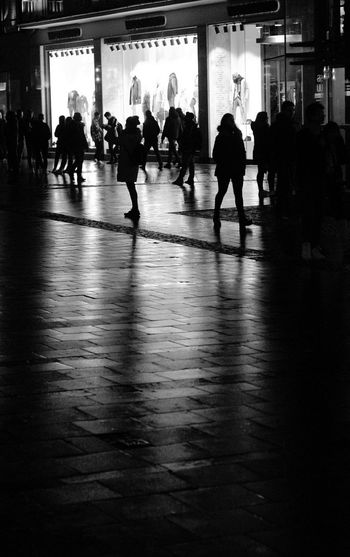 Silhouette people walking in front of building