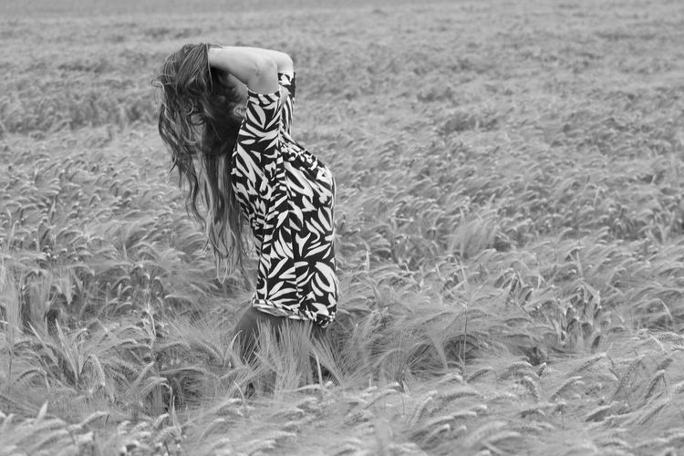 Side view of woman with hands in hair standing on wheat field