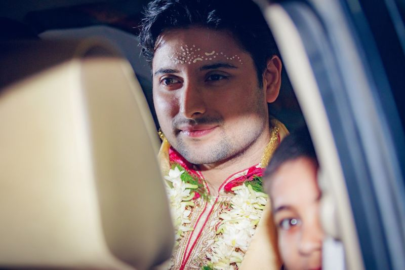 Smiling groom with brother sitting in car