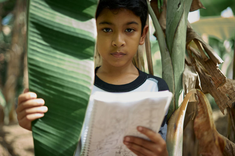 Boy reading book by tree