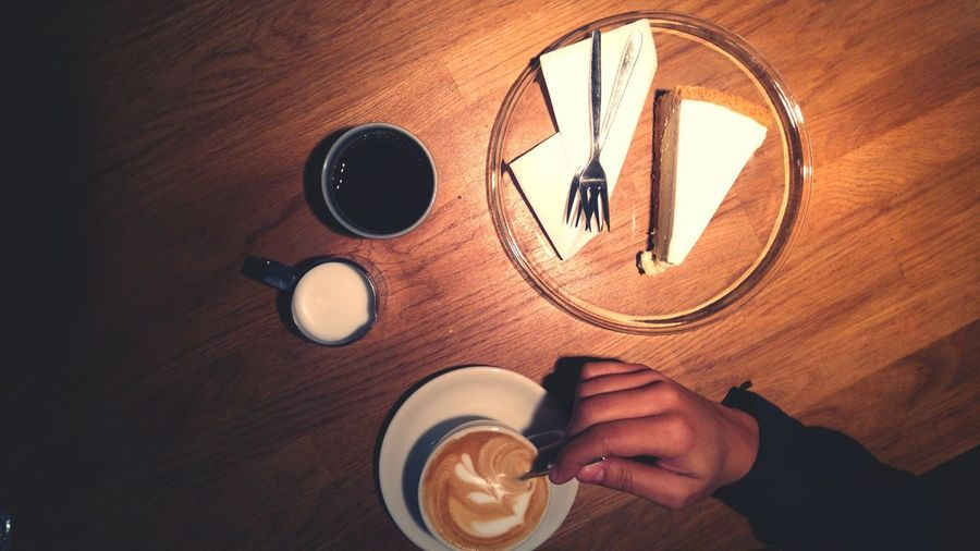 Cropped image of person having coffee and cake on table