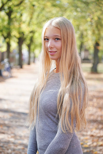 Blond Hair Long Hair Looking At Camera One Person Portrait Beautiful Woman Young Adult Casual Clothing Young Women Day Smiling Lifestyles Leisure Activity Real People Women Outdoors Straight Hair Teenager Female Girl Sweater Spring Autumn Sunny Nature Park