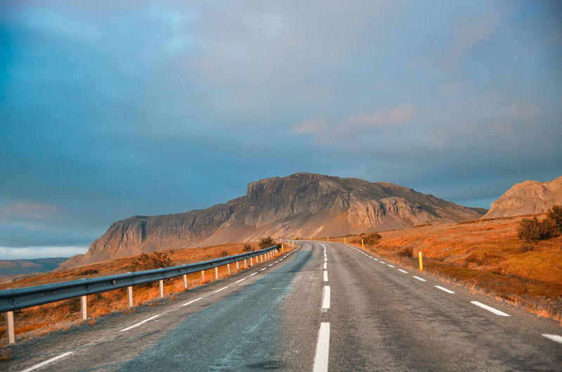Empty road along mountain against sky
