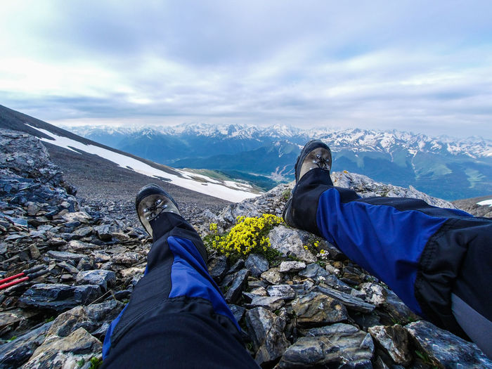 Photos about where these two legs have visited :) And here the feet rest on the rocky slope of the rocky mountains. In the distance, snow-capped mountain peaks are visible, and above them is the sky, covered with clouds. Nearby grow some yellow flowers. Travel Travel Photography Traveling Travelling Beauty In Nature Body Part Cloud - Sky Environment Human Body Part Human Foot Human Leg Legs Leisure Activity Lifestyles Low Section Mountain Mountain Range Nature One Person Outdoors Personal Perspective Real People Sky Travel Destinations Unrecognizable Person