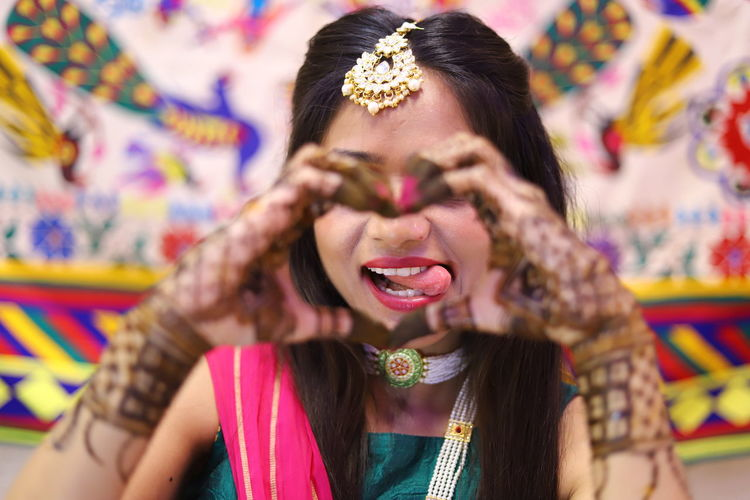 Woman making heart shape and sticking out tongue during haldi ceremony