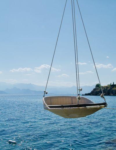 Sailboat moored on sea against sky