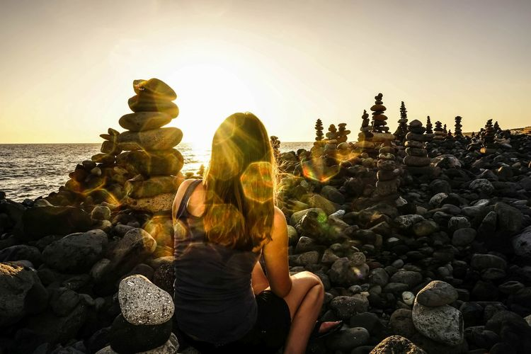 Rear view of woman sitting by stone stacks at sea shore against sky during sunset
