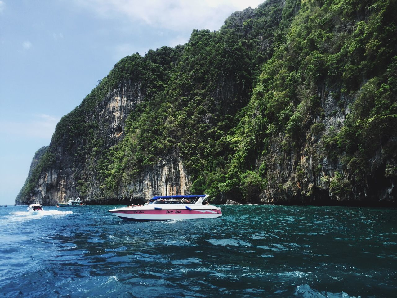 nautical vessel, rock formation, water, sea, transportation, nature, mode of transport, rock - object, mountain, scenics, beauty in nature, waterfront, cliff, day, outdoors, sky, longtail boat, travel destinations, no people, sailing, wake