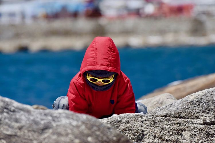 View of kid playing lakeside Changu Lake Childhood Close-up Day Hooded Shirt Lake Lifestyles Mountain Nature One Person Outdoors People Real People Rock - Object Sikkim Tsomgo Lake Water