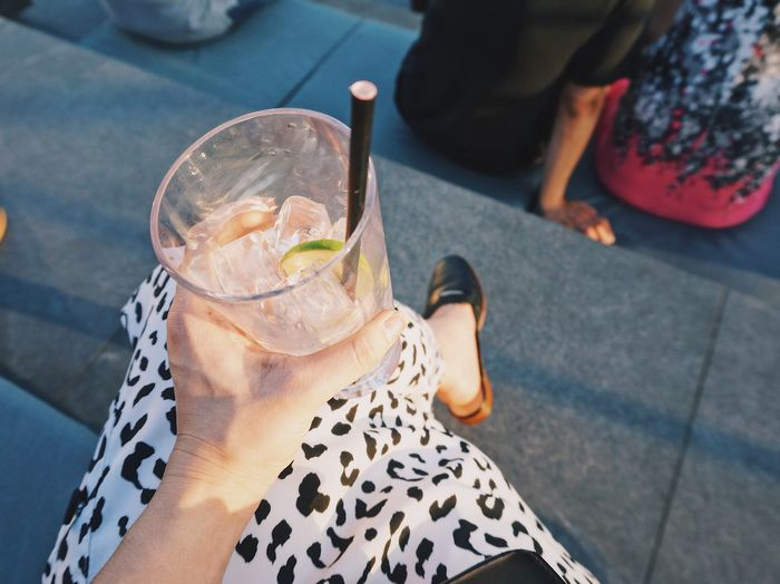 Low section of woman holding drink