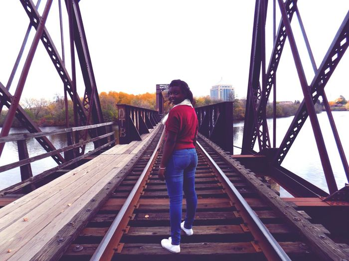 A girl is on the bridge, looking back one more time before she move on down the rails. Bridge Girl Looking At Camera Lookingback Pastispast Moveforward
