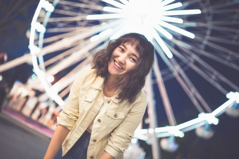 Beautiful asian girl in an amusement park at nght, smiling. ferris wheel in the background