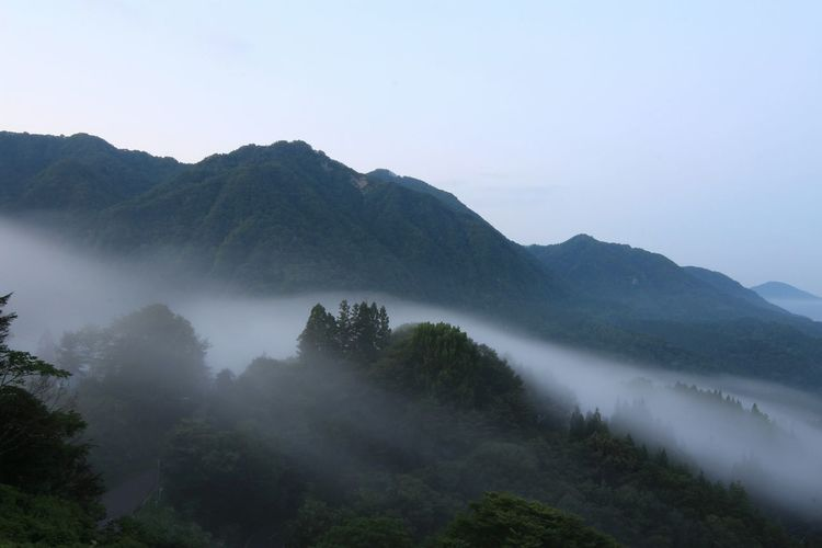 Scenic View Of Green Mountains Against Sky During Foggy Weather